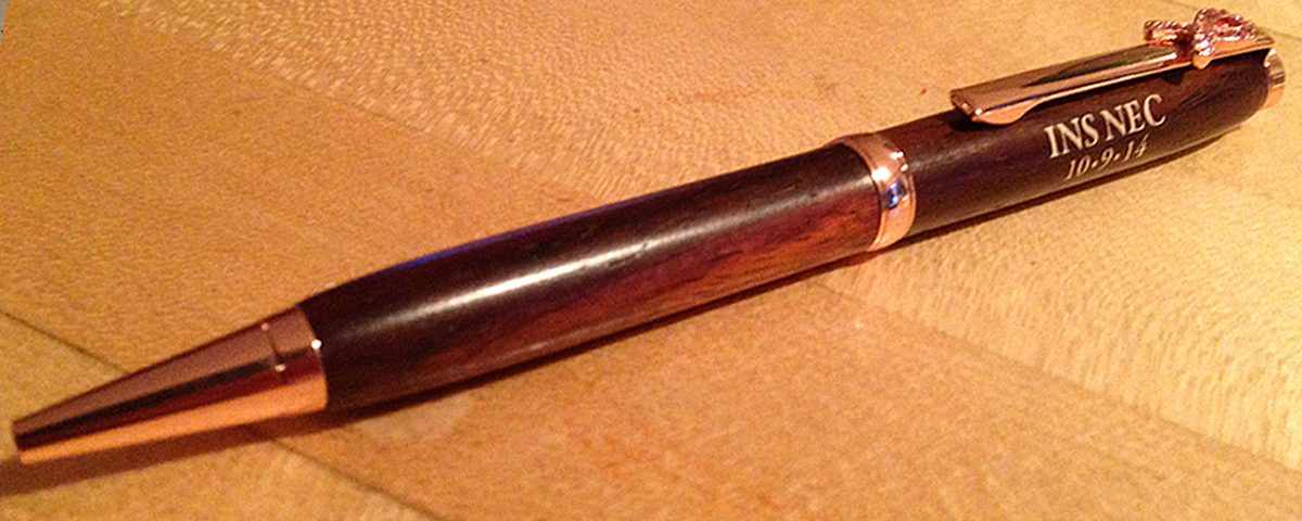 Custom rosewood pen with engraving and color filled lettters.