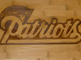 Laser engraved bamboo cutting board with Patriots logo.