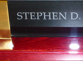 High gloss rosewood finish nameplate with gold metal accents and black silk screened glass upright.